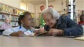 Child reading to senior lady